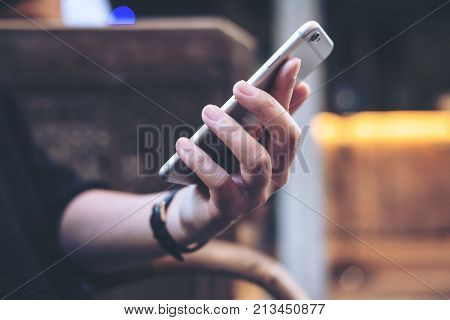 Closeup image of a woman's hands holding using and looking at smart phone in modern cafe