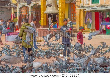 KATHMANDU, NEPAL OCTOBER 15, 2017: Unidentified people walking in the square surrounding of hundred of pigeons in front of a huge bell under a stoned gold structure in Kathmandu Boudhanath Stupa in Boudha town, Nepal.