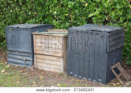 Three Compost Bin In The Garden. Composting Pile Of Rotting Kitchen Fruits And Vegetable Scraps