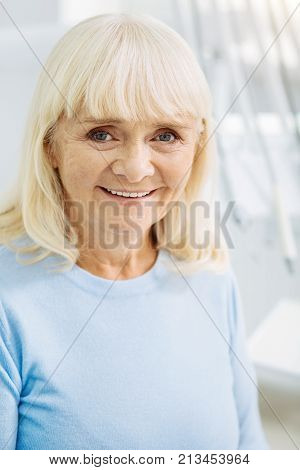 Adorable mood. Close up of cheerful woman expressing bright emotions while looking at you and being pleased