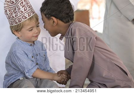 Nizwa Oman 10th Nobember 2017: omani kid and european kid giving eachother an eskimo kiss