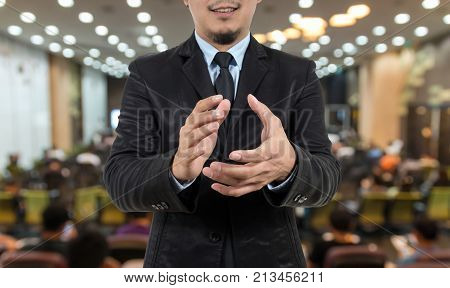 Closeup Businessman clapping and smiling on Abstract blurred photo of conference hall or seminar room with speakers on the stage and attendee background business learning success concept