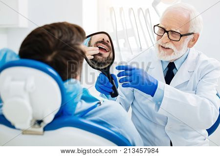 Good job. Pleased patient lying on the couch and looking at his teeth while skilled dentist holding a mirror in hand and expressing concern