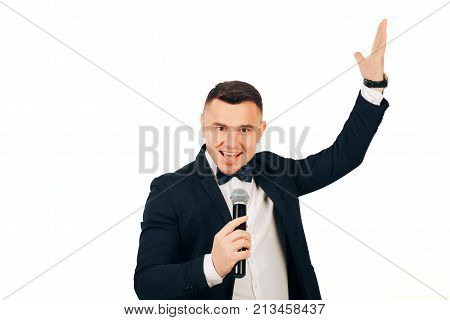 Smiling young anchorman with a microphone in hands on a velom background