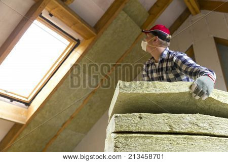 Man installing thermal roof insulation layer - using mineral wool panels. Attic renovation and insulation concept