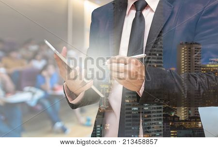 Double exposure of Businessman using the tablet on the Abstract blurred photo of conference hall or seminar room with attendee background, 3D illustration
