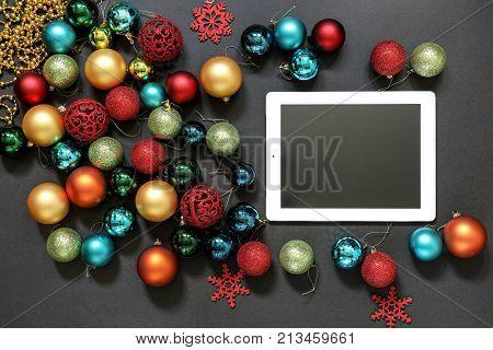 Christmas Tree Toys Balls And Ipad On Dark Background.