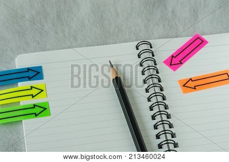 financial target or checklist concept as selective focus on pencil on white paper notebook with arrow stick paper.