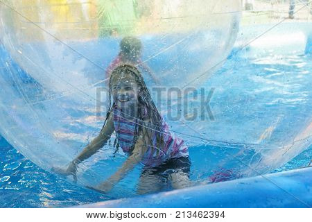 Funny girl on roller coaster aquazorbing.The joy of a child in motion and turning inside the zorb
