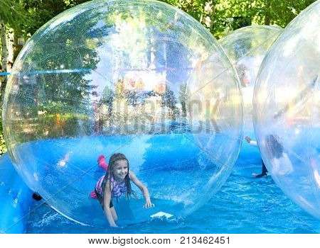 Attraction on the water - zorbing.The joy of a child in motion and turning inside the zorb