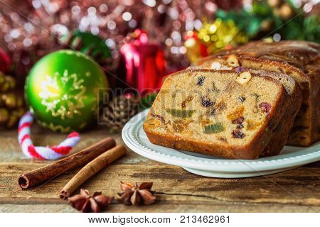 Homemade delicious soft and moist rum fruits cake or Christmas fruits cake with rich dried fruit and nuts slices on wood plate put on wood table with copy for party and celebration. Rum fruit cake for Christmas celebration ready to served.