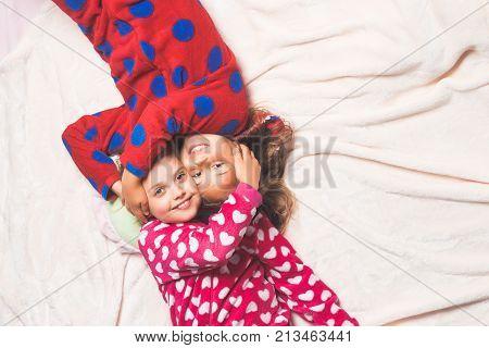 Happy childhood family love friendship. Girl sisters in pajamas hug in bed top view. Children nightwear fashion. Bedtime slumber dream sleepover. Comfort home concept.
