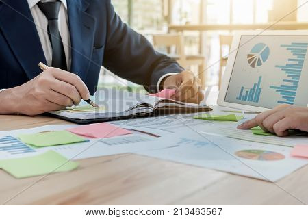 young business man hoding pen point notebook with partner using tablet graph chart and post it note for Plans to improve quality next month.