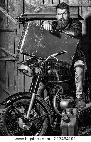 Frown bearded man hipster biker brutal male with beard and moustache in leather jacket sits on motorcycle with vintage suitcase and gas can on wooden background