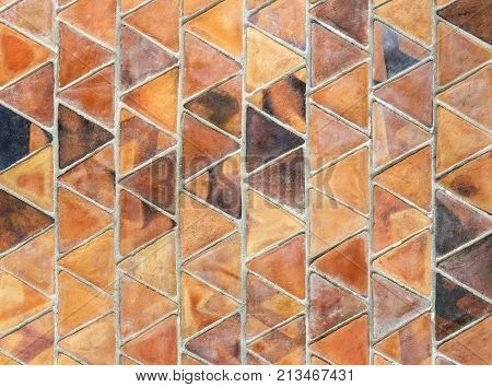 a triangle slab of baked clay used in overlapping rows for covering the wall. banked clay wall texture for background.