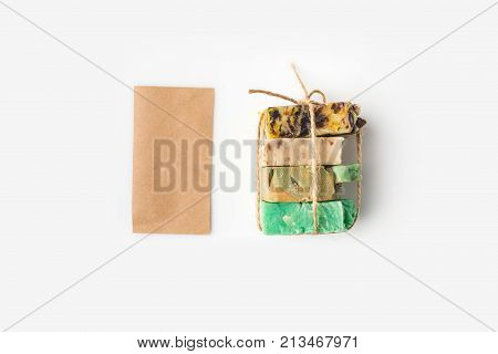 top view of various handcrafted soap tied with thread on white surface poster