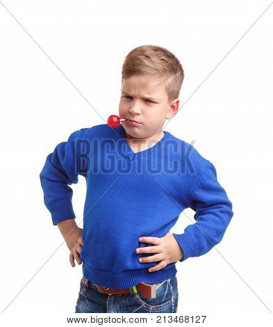 A boy in a blue sweater with a stick with a lollipop in his mouth is standing arms in the sides. With a menacing and serious look on a white isolated background