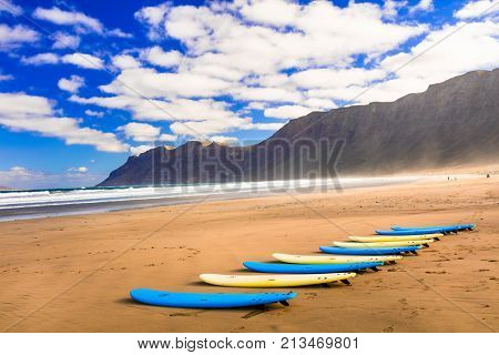 Surfboards on wide sandy beach Famara - famous beach for surfing in Lanzarote island