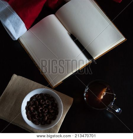 Planning Future On Christmas: A Notebook With Blank Pages, A Black Pen, Santa Hat, Glass Mug With Te