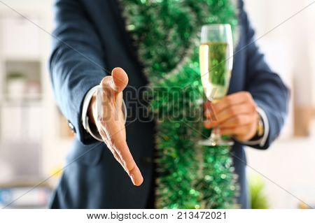 Man in suit hold champagne goblet give arm as hello in office closeup. Friend welcome mediation offer positive introduction thanks gesture summit participate approval motivation male strike bargain