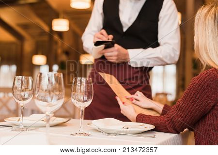Cropped image of Waiter writing down the order of customer at the restaurant