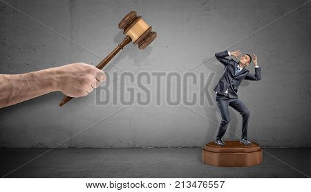 A tiny scared businessman stands on a giant sound block under a large hand holding a judge gavel. Business and law. Legal prosecution. Contract breach.