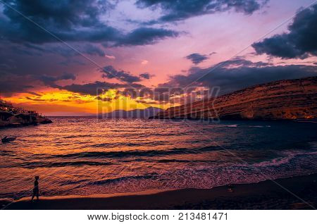 Sunset at Matala beach on Crete island, Greece. There is a girl walking on the beach. The colors in the sky are very beautiful yellow orange and red.