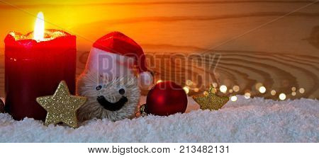 Christmas snowman with santa claus hat isolated on wood background. Red Advent candle and Snowman.