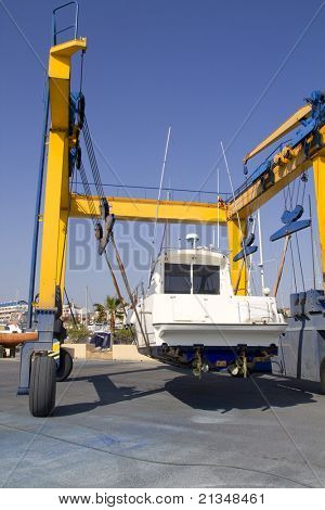 boat yellow travelift crane holding motorboat under blue sky