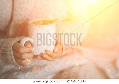 Famale hands holding a cozy ceramic handmade mug with coffe. Winter and Christmas home time concept. Lifestyle. Copy space. Festive background with bokeh and sunlight. Magic fairy tale