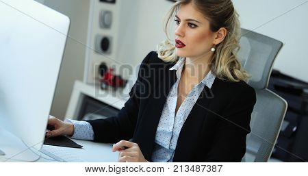 Overworked businesswoman staying in office late to work