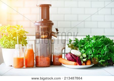 Woman making fresh drink. Juicer and carrot juice. Fruits in background. Clean eating, detox concept. Sunny morning with sunlight. Toned effect