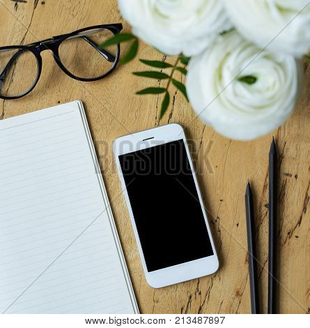 Top view of the white mobile phone with blank copy space screen for advertisement content blank notepad glasses black pencils and bouquet of white flowers ranunculus on a wooden table. Flat lay.