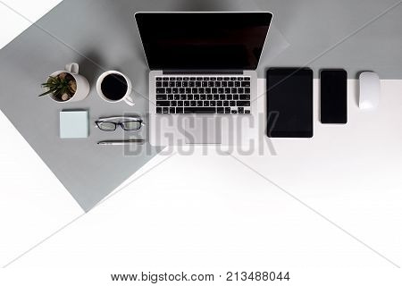 Flat lay photo of Office table with laptop computer notebook digital tablet mobile phone Pencil eyeglasses on modern two tone (white and grey) background. Desktop office mockup concept.