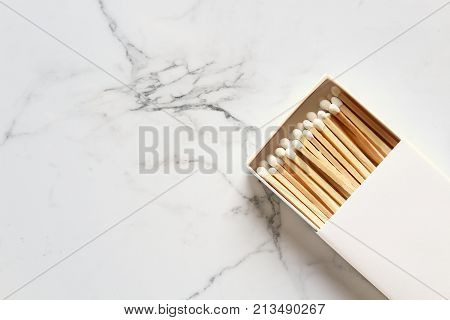 White match box filled with match sticks against white marble copy space.