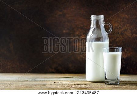Milk bottle and milk glass on wooden table. Healthy eating conceptMilk bottle and glass on wooden table, dark background. Healthy eating concept. Copy space.