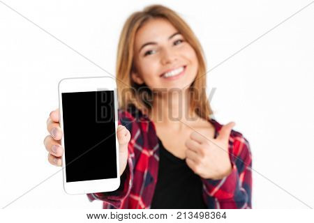 Close up portrait of a smiling cheerful girl showing blank screen mobile phone and giving thumbs up isolated over white background, focus on mobile phone