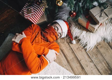 Guy is lying on the floor near christmas tree with his arms crossed and sleeping. He has a hat on his head and a sweter's neck on his mouth. It's apparently cold in room after in the morning after celebrating Christmas eve. Cut view