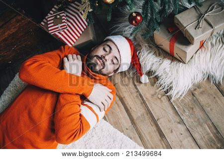 A picture of adult man lying on the floor quite close to the Christman tree and sleeping fter big Christmas party was over. He has crossed the arms on the chest and trying to get some warmth because it's cold in room in the moring. Close up. Cut view