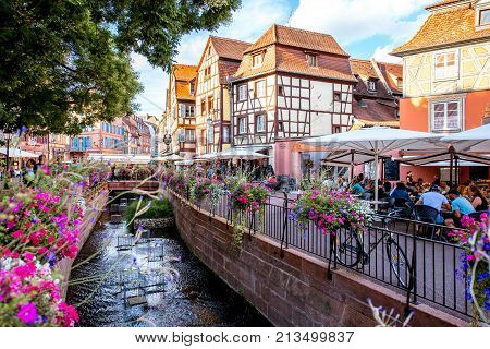 COLMAR, FRANCE - July 26, 2017: Landscape view on the beautiful colorful buildings on the water channel with bars and restaurants in the famous tourist town Colmar in Alsace region, France