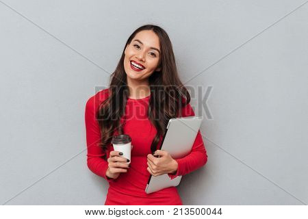 Smiling brunette woman in red blouse holding laptop computer and cup of coffee while looking at the camera over gray background