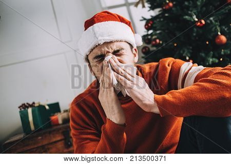 One more picture of a sick man using his white tissue and sneezing into it. He woke up being sk with temperature and headache after celebrating Christmas holiday. He took some medicine and waiting until it will work. Close up. Cut view