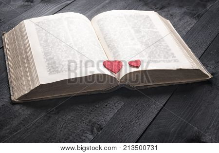Two red hearts on an aged book - Schooling theme image with an antique open book and two red hearts on its pages displayed on a vintage wooden table. A concept for reading studying or romance.