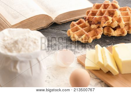 Waffles with ingredients and cookbook - Delicious homemade Belgian waffles surrounded by the ingredients for their baking flour butter eggs and an open recipe book on a rustic table.