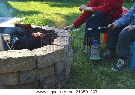 Two boys are grilling or barbecuing Polish sausages over an open fire pit in their backyard