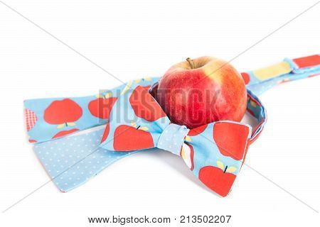funny tie bow with big red polka dots in front of red apple, close up, fruit, fresh.