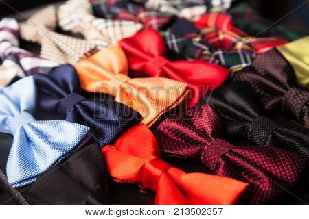 Collection of colorful and varieties of pattern bow ties texture background in the middle on a wooden tray.