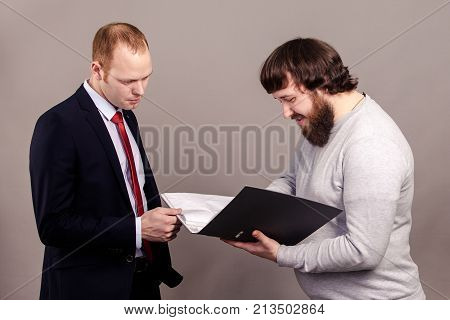 The professor in jumper checks the student in suit essay.