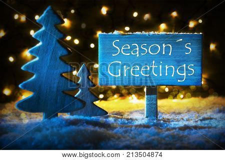 Sign With English Text Seasons Greetings. Blue Christmas Tree With Snow And Magic Glowing Lights In Backround. Card For Seasons Greetings.
