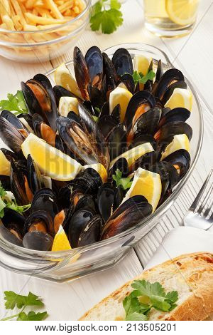 A large glass dish with mussels and lemon stands on a table